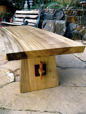Mesa de Bayo <br /> Curved Bench or Coffee Table<br /> Figured Myrtle with Bubinga collars and Tigerwood pins<br /> with Koa heart inlay <br /> 47L x 18W x 18.8H